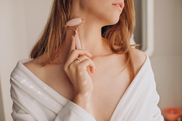Kobieta wykonująca masaż za pomocą wałka do twarzy z kwarcu różanego