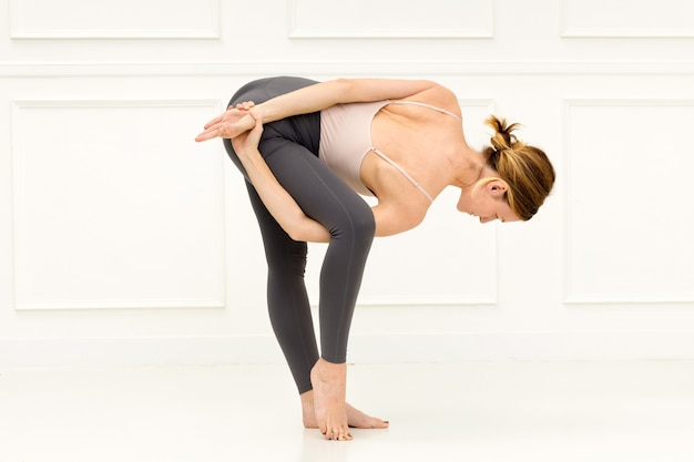 Kobieta wykonująca odmianę uttanasany lub stojąca pozycja jogi z pochyleniem do przodu na udo