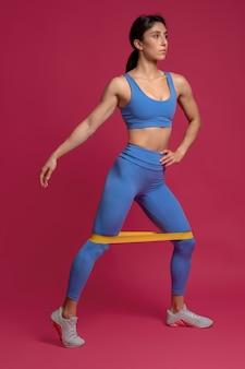 Kobieta wykonująca trening dolnej części ciała z taśmą oporową na bordowej ścianie