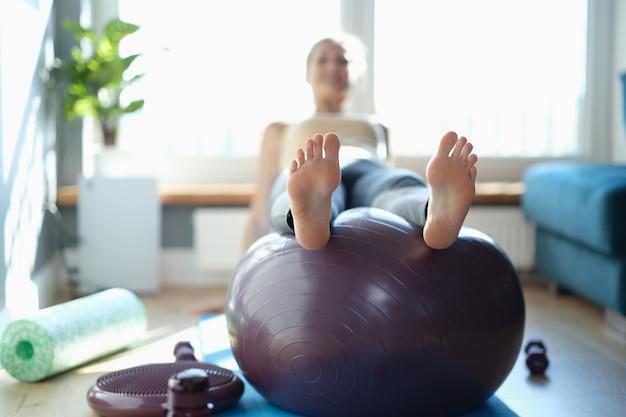 Kobieta wykonuje ćwiczenia sportowe na piłkę w domu. fitball dla idealnej sportowej koncepcji ciała