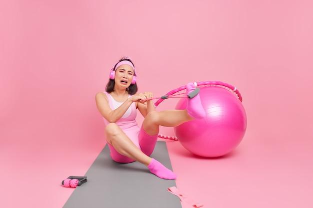 Kobieta wykonuje ćwiczenia z taśmą oporową rozciąga nogi używa ekspandera ma trudne pozy treningowe na macie ubrana w strój sportowy ma na uszach słuchawki.
