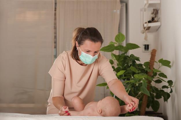 Kobieta wykonuje masaż noworodkowi w masce medycznej.