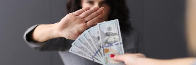 Kobieta wykonuje negatywny gest w zamian za pieniądze na jej odmowę przyjęcia koncepcji łapówki
