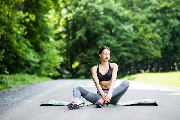 Kobieta wykonuje rozciąganie przed uprawianiem sportu w parku na świeżym powietrzu