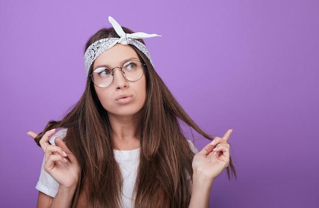Kobieta wykręca włosy w dłoniach i patrzy w bok z namysłem.