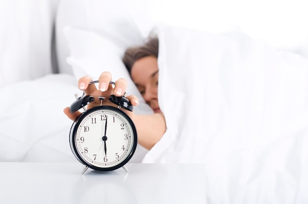 Kobieta wyłączająca budzik