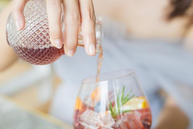 Kobieta wylewa do szklanki świeżego drinka koktajl ze szklanej butelki z sałatką owocową w szklance.