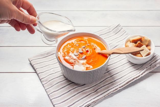 Kobieta wylewa śmietankę w zupie dyniowej-puree z bułką tartą i nasionami, białe drewniane tła.