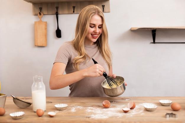Kobieta wymieszaj jajka i mleko w metalowej misce