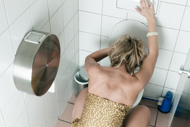 Kobieta wymiotuje w toalecie