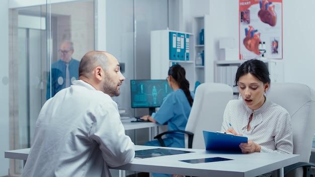 Kobieta wypełniająca formularze, pytająca lekarza o coś, czego nie wie. opieka zdrowotna w nowoczesnym szpitalu lub przychodni prywatnej, profilaktyka chorób i konsultacje w gabinecie lekarskim leczenie leków diag