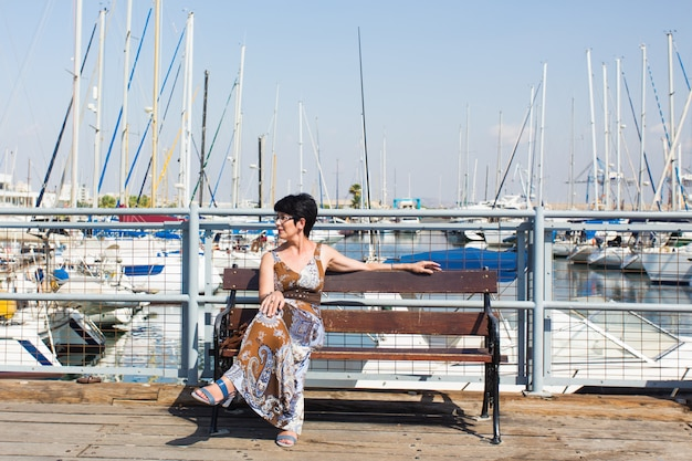 Kobieta wypoczynek na wakacjach w pobliżu mariny jachtów i żaglówek miejscowości wypoczynkowej.