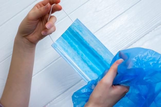 Kobieta wyrzuca maskę medyczną. wykorzystanie ochrony podczas koronawirusa. koniec pandemii. zakończenie czasu kwarantanny. niebieski worek na śmieci.