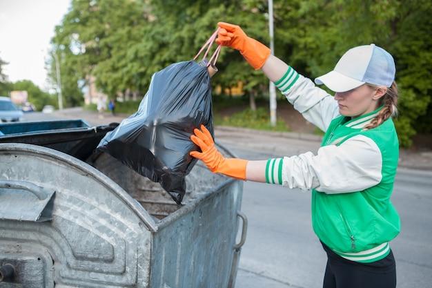 Kobieta wyrzuca worek na śmieci do kosza na zewnątrz w mieście