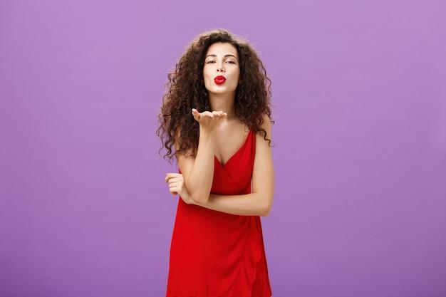 Kobieta wysyłająca namiętny pocałunek będąca beznadziejną romantyczną stojącą w eleganckiej czerwonej sukience z kręconą fryzurą i makijażem, dmuchająca mwah z uśmiechem i złożonymi ustami trzymająca dłoń przy ustach nad fioletową ścianą.