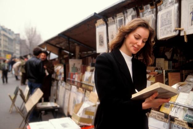 Kobieta wyszukuje przy bookstand, paryż, francja