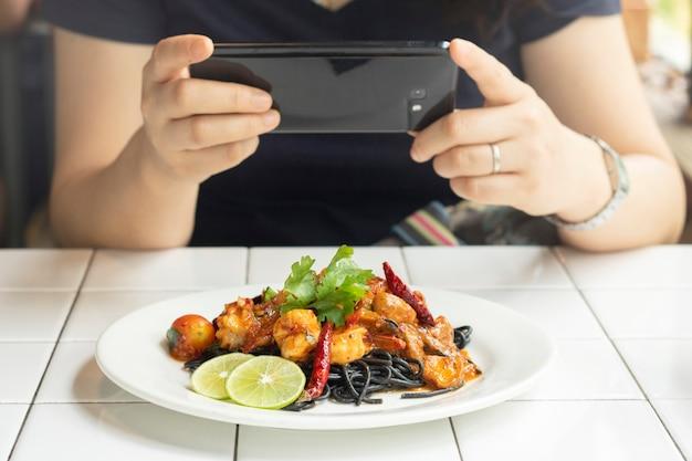 Kobieta wziąć zdjęcie żywności z telefonu komórkowego spaghetti węgiel drzewny owoce morza na stole w restauracji