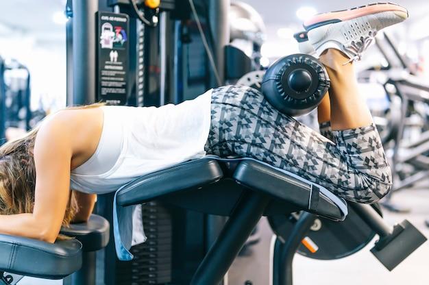Kobieta wzmacnia nogi w maszynie siłowni