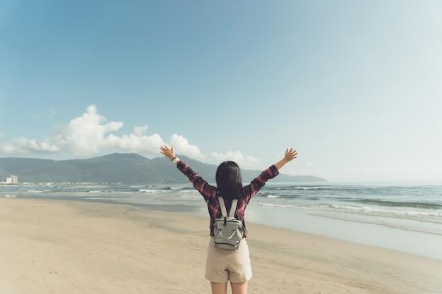 Kobieta wzrost wręcza do niebo wolności pojęcia z niebieskim niebem i latem