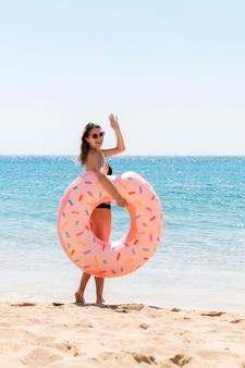 Kobieta wzywa do pływania w morzu i macha ręką. dziewczyna relaksuje się z pączkiem na plaży i bawi się nadmuchiwanym pierścieniem. letnie wakacje i koncepcja wakacji.