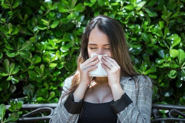 Kobieta z alergią na pyłki kicha z zamkniętymi oczami