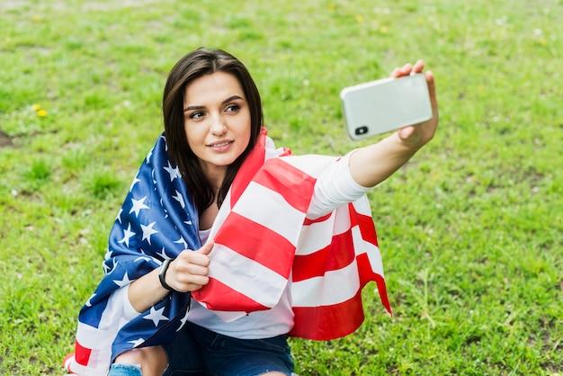 Kobieta z amerykańską flagą biorąc selfie