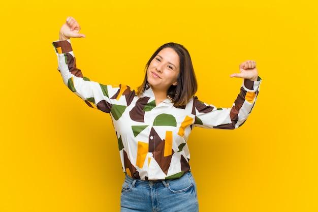 Kobieta z ameryki łacińskiej czuje się dumna, arogancka i pewna siebie, wygląda na zadowoloną i odnoszącą sukcesy, wskazując na siebie na żółtej ścianie