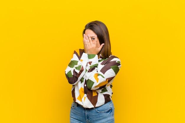 Kobieta z ameryki łacińskiej czuje się przestraszona lub zawstydzona, zerkając lub szpiegując oczy na wpół zakryte izolowanymi rękami