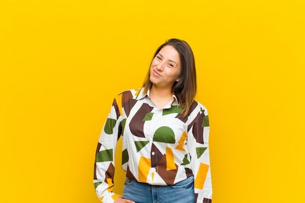 Kobieta z ameryki łacińskiej, wyglądająca na szczęśliwą i przyjazną, uśmiecha się i mruga do ciebie z pozytywnym nastawieniem na białym tle na żółtej ścianie