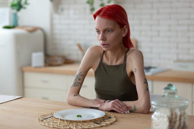 Kobieta z anoreksją. anorektyczka, rudowłosa kobieta, która wygląda okropnie siedząc przy talerzu z tylko trzema zielonymi groszkami