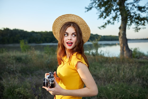 Kobieta z aparatem patrząc w ten sposób czerwone usta kapelusz podróż wypoczynek charakter
