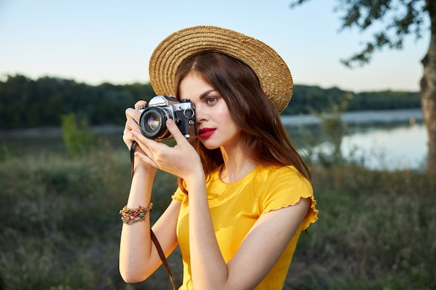 Kobieta z aparatem patrzy w obiektyw aparatu natura świeże powietrze podróży