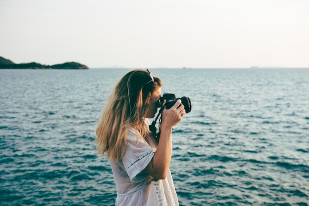 Kobieta z aparatem strzelającym na plaży