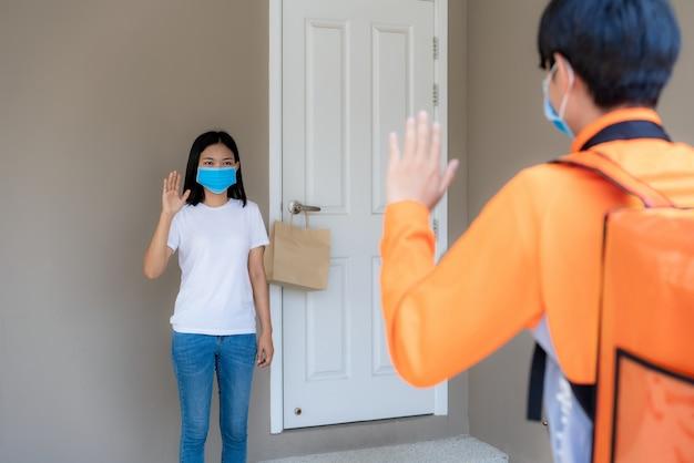 Kobieta z azji podnosi torebkę z dostawą z gałki drzwi i wita się z rowerzystą bezdotykowo lub bez kontaktu z dostawcą z rowerem przed domem, aby zdystansować się od ryzyka infekcji. koncepcja koronawirusa