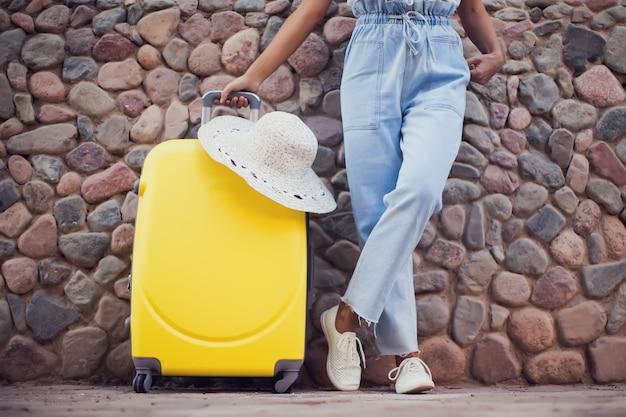 Kobieta z bagażem i kapeluszem na zewnątrz. koncepcja podróży, wakacji i stylu życia