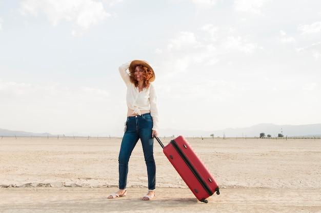 Kobieta z bagażem w naturze