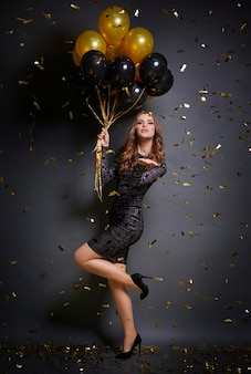 Kobieta z balonami dmuchająca buziaka