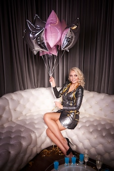 Kobieta z balonem siedzi na kanapie na przyjęciu sylwestrowym