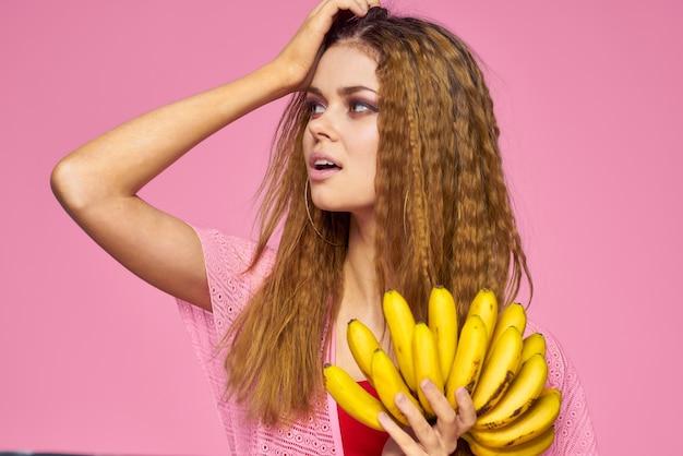 Kobieta z bananami faliste włosy owoce jasny makijaż styl życia