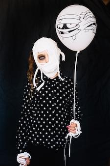 Kobieta z bandażą twarzy gospodarstwa balonu