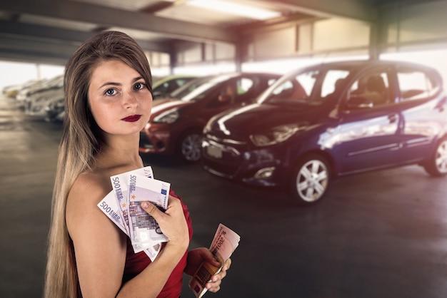 Kobieta z banknotami euro w garażu kupując samochód