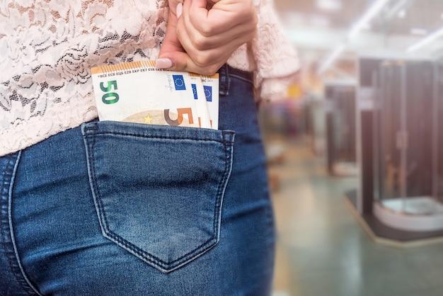 Kobieta z banknotów euro w dżinsach, kupując kabinę prysznicową