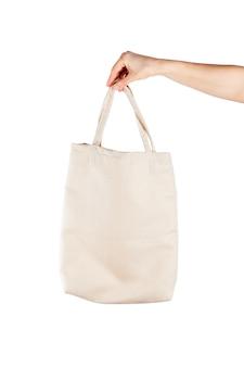Kobieta z bawełnianą eco torbą nad białym backgound. ekologia lub koncepcja ochrony środowiska. biała eco torba na makiety
