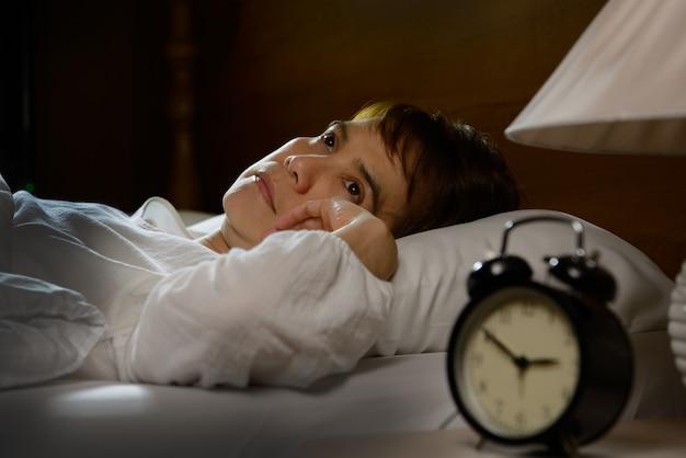 Kobieta z bezsennością, leżąc w łóżku z otwartymi oczami