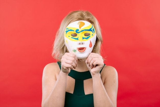 Kobieta z białą karnawałową maską w rękach