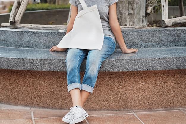 Kobieta z białą pustą bawełnianą torbą w parku