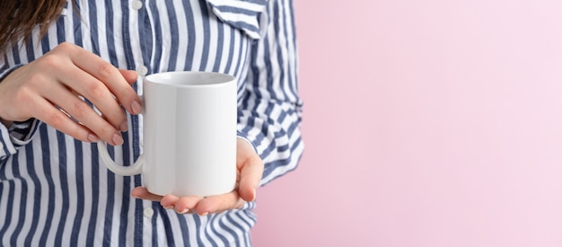 Kobieta z białym kubkiem na stole w minimalistycznym wnętrzu