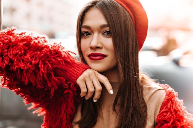 Kobieta z białym manicure i czerwonymi ustami patrzy na aparat na tle ulicy. kobieta ubrana w czerwony beret i wełnianą kurtkę oparła się o okno.