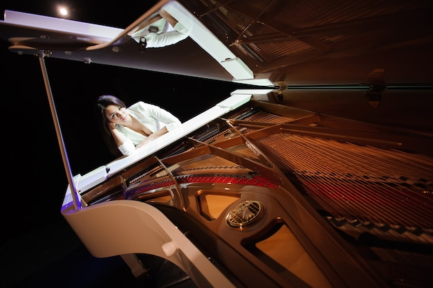 Kobieta z białym pianinem na scenie.
