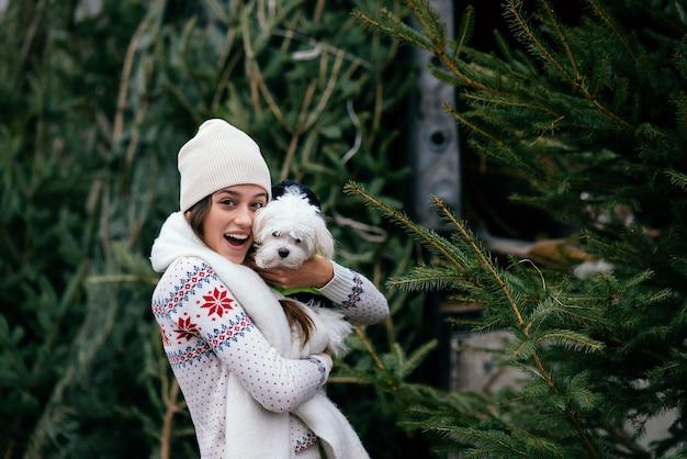 Kobieta z białym psem na rękach w pobliżu zielonych choinek na targu